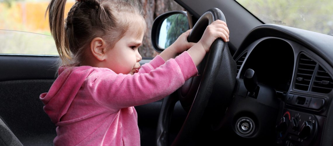 Little girl sitting behind the wheel of a car with a busy face, outdoors, family travel concept