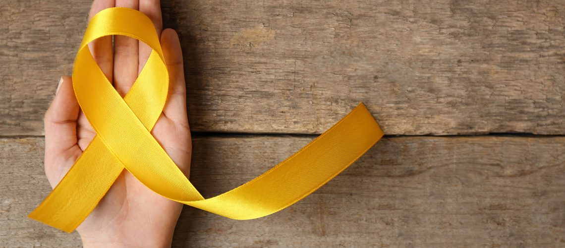 Yellow awareness ribbon in female hand on wooden background